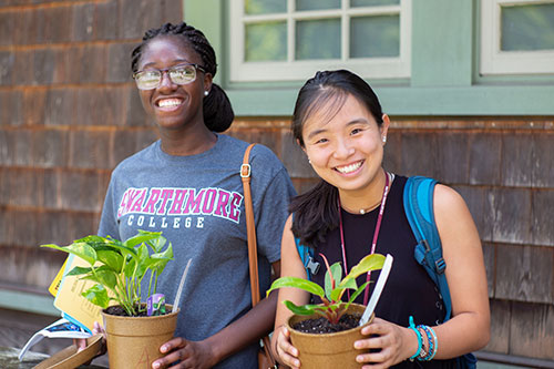 Photo of two students holding plants